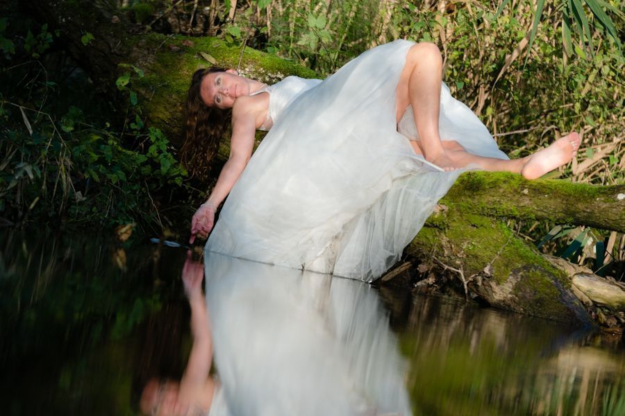 Trash the Dress Shooting liegend auf Baumstamm